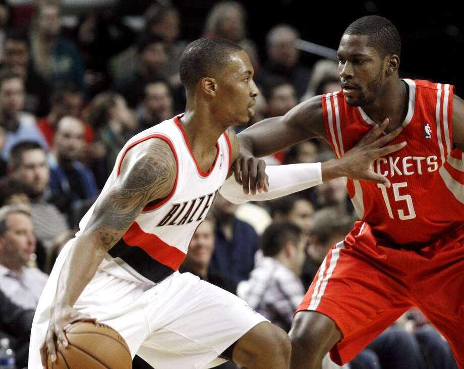 Blazers guard Damian Lillard, left, works the ball against Rockets guard Toney Douglas. (Don Ryan / Associated Press)