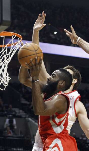 Rockets guard James Harden, left, goes to the hoop against Blazers forward Victor Claver. (Don Ryan
