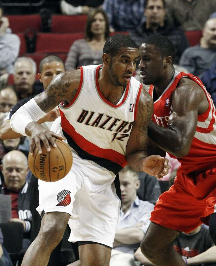 Blazers forward LaMarcus Aldridge, left, works the ball in against Rockets forward Patrick Patterson. (Don Ryan / Associated Press)