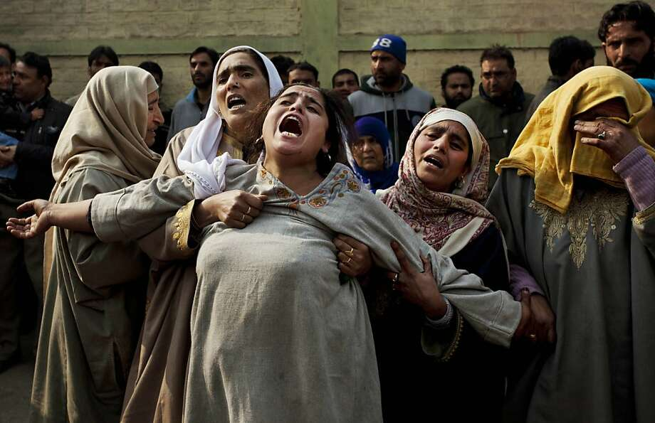Kashmiri Muslim women comfort a wailing relative of Mushtaq Ahmed during his funeral procession in Srinagar, India, Friday, Nov. 16, 2012. Unidentified gunmen Thursday opened fire at a liquor shop on the banks of Dal Lake killing Ahmed and injuring four more, police said. Photo: Dar Yasin, Associated Press