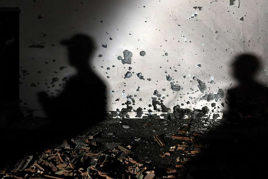 Israeli soldiers examine a damaged wall of a house hit by a rocked fired from the Gaza Strip at Be'er Tuvia Regional Council, Friday, Nov. 16, 2012. Fierce clashes between Israeli forces and Gaza militants are continuing for the third day. Photo: Tsafrir Abayov, Associated Press