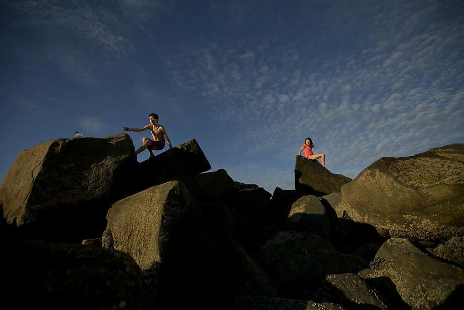 Grant, left, reaches for a scuba mask as his sister Elizabeth, right, rests on a rock formation as their family visited the beach in Coronado, Calif. on Friday, Nov. 16, 2012. Photo: Gregory Bull, Associated Press