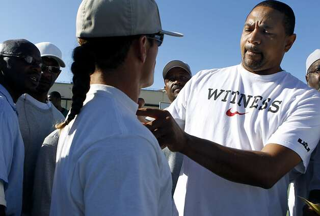 Golden State Warriors head coach Mark Jackson autographs an inmate's shirt before playing in a basketball game against the San Quentin Warriors at San Quentin State Prison on Saturday, Sept. 22, 2012. Photo: Paul Chinn, The Chronicle