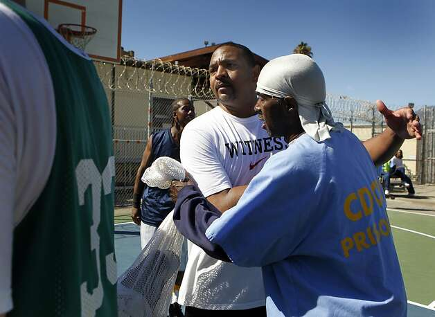 Golden State Warriors head coach Mark Jackson (center) hugs an inmate after a basketball game against the San Quentin Warriors at San Quentin State Prison on Saturday, Sept. 22, 2012. Photo: Paul Chinn, The Chronicle