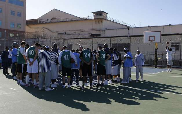 Players from both teams gather at mid-court before a basketball game between employees of the Golden State Warriors and the San Quentin Warriors at San Quentin State Prison on Saturday, Sept. 22, 2012. Photo: Paul Chinn, The Chronicle