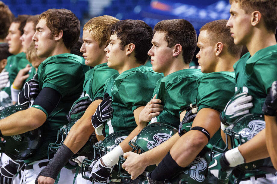The Reagan Rattlers stand at attention as the National Anthem is sung prior to their Class 5A Division II first round game with Smithson Valley at the Alamodome on Nov 16, 2012.  MARVIN PFEIFFER/ mpfeiffer@express-news.net Photo: MARVIN PFEIFFER, Express-News / Express-News 2012