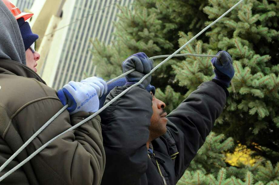OGS grounds workers Nick Carnavale, left, and Juan Thomas hold a tether line as the Christmas tree at the Empire State Plaza is put in place in Albany, NY Friday Nov. 16, 2012. (Michael P. Farrell/Times Union) Photo: Michael P. Farrell