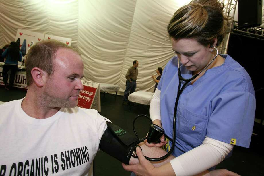 Mike Geller gets his blood pressure taken by Dr. Sarah Gamble before the start of the Harvest Time Church fourth annual Run for Africa Saturday, Nov. 16, 2012. Photo: DAVID AMES / GREENWICH TIME FREELANCE