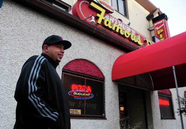 Arthur's Famous Pizza has reopened after closing two years ago when the owner, Arthur Yiotos, died.  Customers are thrilled the Bridgeport institution is back.  Miguel Miranda, of Bridgeport, waits for his carry-out order Thursday, Nov. 15, 2012. Photo: Autumn Driscoll / Connecticut Post