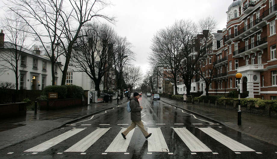"FILE - In this file photo taken Feb. 16, 2010, a man walks on the zebra crossing  made famous from the album cover of The Beatles' 'Abbey Road' in front of Abbey Road Studios, seen at left, in London. It's a mystery tour, but it's hardly magical. More than nine miles from the striped crosswalk made famous by the Beatles album ""Abbey Road,"" this drab transit station in east London keeps drawing confused fans of the Fab Four into unwanted jaunts through a gritty, industrial area just south of London' Olympic Stadium. Abbey Road Station has no relation to the Beatles' Abbey Road Studios, the birth place of the eponymous album and a London tourist landmark. The glass-and-metal station is wedged between a train depot, warehouses, and gloomy public housing projects, a world away from the leafy, suburban street pictured on the album's cover.  (AP Photo/Akira Suemori, File) Photo: AKIRA SUEMORI"