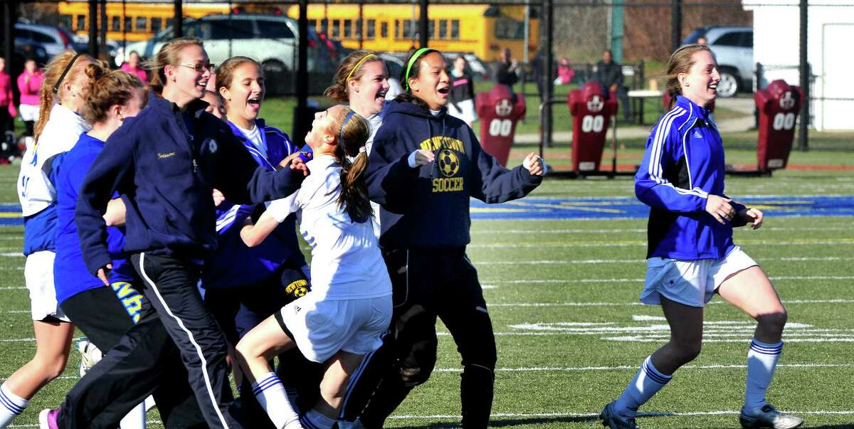 Newtown High School girls soccer celebrates beating New Milford in the Class LL state semifinals at Waterbury Saturday, Nov. 17, 2012.