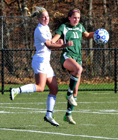 Newtown High School's Amy Martin, left, and New Milford's Olivia Knight compete in the Class LL state semifinals at Waterbury Saturday, Nov. 17, 2012. Photo: Michael Duffy