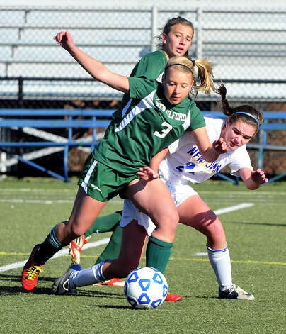 New Milford High School's Jennifer Milar, left, and Newtown's Brenna Kelly compete in the Class LL state semifinals at Waterbury Saturday, Nov. 17, 2012. Photo: Michael Duffy