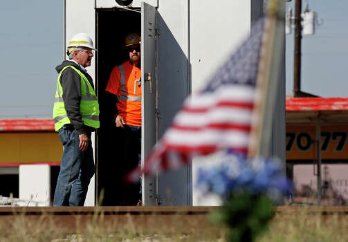 Workers check railroad crossing signals, Saturday Nov. 17, 2012, in Midland, Tx., at the intersection where a Union Pacific train struck a float carrying military veterans,Thursday Nov. 15, 2012, killing four men, including one from the San Antonio area. American flags and flowers were placed at the site after the accident. Photo: Edward A. Ornelas, San Antonio Express-News / © 2012 San Antonio Express-News