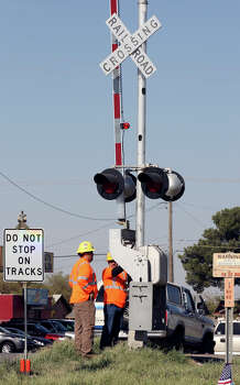 Workers check railroad crossing signals, Saturday Nov. 17, 2012, in Midland, Tx., at the intersection where a Union Pacific train struck a float carrying military veterans,Thursday Nov. 15, 2012, killing four men, including one from the San Antonio area. Photo: Edward A. Ornelas, San Antonio Express-News / © 2012 San Antonio Express-News
