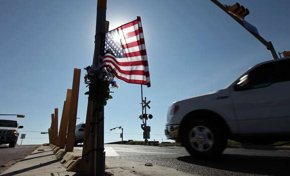 An American flag and flowers left at the at the intersection, Saturday Nov. 17, 2012, in Midland, Tx., where a Union Pacific train struck a float carrying military veterans onThursday Nov. 15, 2012, killing four men, including one from the San Antonio area. Photo: Edward A. Ornelas, San Antonio Express-News / © 2012 San Antonio Express-News