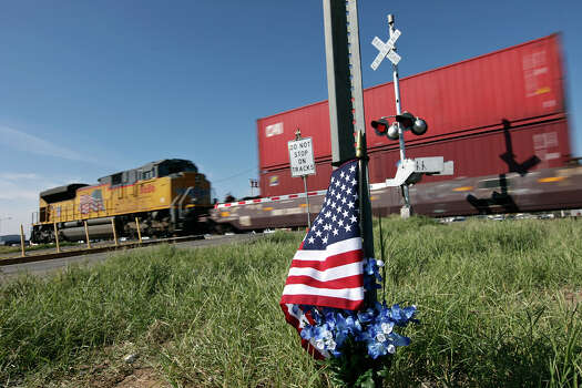 A Union Pacific train passes an American flag and flowers Saturday Nov. 17, 2012, in Midland, Tx., at the intersection where a Union Pacific train struck a float carrying military veterans,Thursday Nov. 15, 2012, killing four men, including one from the San Antonio area. Photo: Edward A. Ornelas, San Antonio Express-News / © 2012 San Antonio Express-News