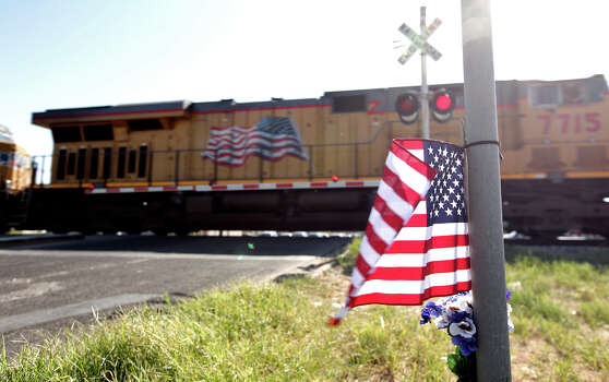 A Union Pacific train passes an American flag and flowers Saturday Nov. 17, 2012, in Midland, Tx., at the intersection where a Union Pacific train struck a float carrying military veterans onThursday Nov. 15, 2012, killing four men, including one from the San Antonio area. Photo: Edward A. Ornelas, San Antonio Express-News / © 2012 San Antonio Express-News