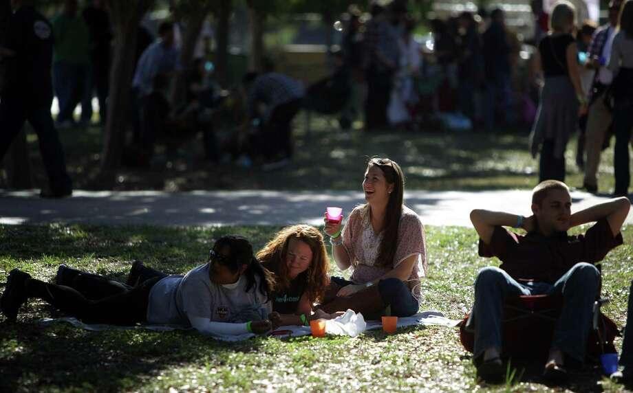 From left: Shakira Dinally, Patricia Johnson, and Allison LaMontagne, enjoy sampling beer under the sun during the beer festival. Photo: Mayra Beltran, Houston Chronicle / © 2012 Houston Chronicle