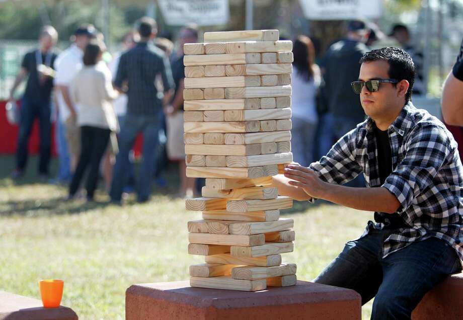 Matthew Villarreal, 24, plays a giant version of Jenga with friends  during the beer festival. Photo: Mayra Beltran, Houston Chronicle / © 2012 Houston Chronicle