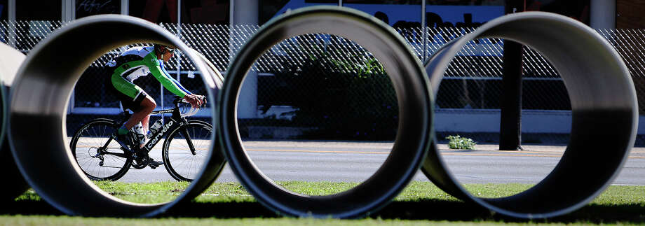 A cyclist is seen through a drainage pipe near Lion's Field Park on Broadway on Saturday, Nov. 17, 2012. Construction at the park had a series of pipes laid out on the grounds. Photo: Kin Man Hui, San Antonio Express-News / @2012 San Antonio Express-News