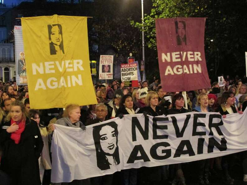 Abortion rights protesters bearing pictures of Savita Halappanavar march through central Dublin, Sat