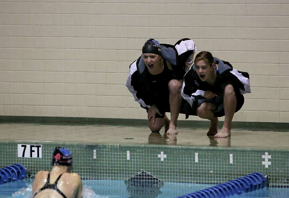 Mike Ross Connecticut Post freelance -Darien High School's Olivia Leunis receives cheering on from teammates Amanda Bieler and Becca Maroney during 200 IM heat during Saturday's State Open Championships at Yale University's Payne Whitney Gym.