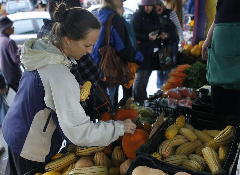 Kate Bartenwerfer shops for Thanksgiving dinner items at San Francisco's Alemany Farmers' Market, where sellers expected a booming day until the Saturday morning rain hit. Photo: Paul Chinn, The Chronicle