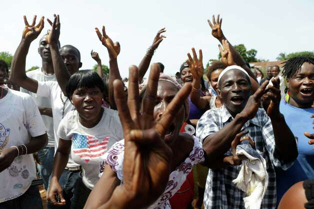 Supporters of incumbent President Ernest Bai Koroma cheer and hold up four fingers to show they want the ruling party to sweep the elections, as Koroma leaves after voting, in Freetown, Sierra Leone, Saturday, Nov. 17, 2012. A decade after Sierra Leone's brutal civil war, voters on Saturday chose between an incumbent president who has provided new roads and free health care and a field of opposition candidates who decry the poverty and pace of economic recovery.(AP Photo/Rebecca Blackwell) Photo: Rebecca Blackwell