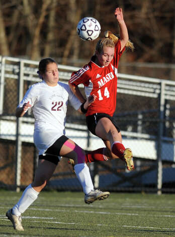 Masuk's Raine Oesterle goes up for a header as East Lyme's Erin Doherty defends during the Class L semifinals Saturday, Nov. 17, 2012 at Municipal Stadium in Waterbury, Conn. Photo: Autumn Driscoll / Connecticut Post