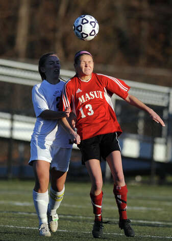 Masuk's Michelle Andrzejewski heads the ball as East Lyme's Lindsay Schneider defends during the Class L semifinals Saturday, Nov. 17, 2012 at Municipal Stadium in Waterbury, Conn. Photo: Autumn Driscoll / Connecticut Post