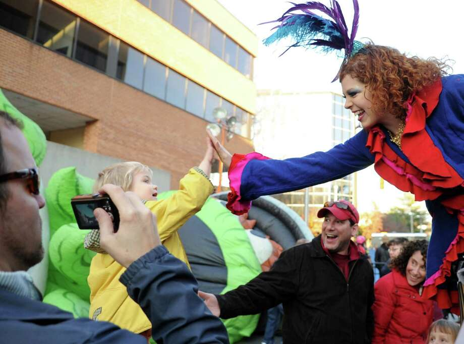 Basil Lintern of Stamford gets a high-five from a woman on stilts as his father, Tom, gets a photo during Saturday's Balloon Inflation Party near the intersection of Summer and Hoyt Streets in Stamford on November 17, 2012. Photo: Lindsay Niegelberg / Stamford Advocate