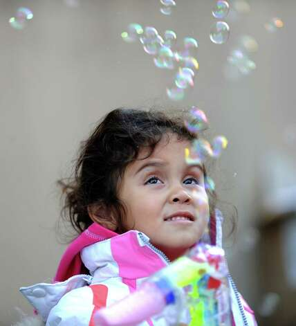 Teresa Cofresi, 4, plays with bubbles during Saturday's Balloon Inflation Party near the intersection of Summer and Hoyt Streets in Stamford on November 17, 2012. Photo: Lindsay Niegelberg / Stamford Advocate