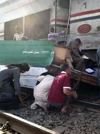 Egyptians search for loved ones after a train hit a school bus near Assiut. Photo: Mamdouh Thabet, Associated Press