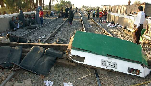 Egyptians block the tracks with debris from the crash and railroad ties at the scene of a train crash that killed at least 49 people, most of them children between 4 and 6 years old near Assiut  in southern Egypt, Saturday, Nov. 17, 2012. Egyptian security officials say grieving families in the central province of Assiut have cut off roads and denied the prime minister access to the scene of a train accident that killed at least 49 kindergartners. (AP Photo) Photo: Uncredited, Associated Press