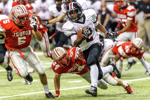 Churchill's Deja Morrow (center) picks up yardage with Judson's Derrick Thomas (left) and Bryce Stoepler in pursuit during the second quarter of their Class 5A Division II first round game at the Alamodome on Nov 17, 2012.  Judson advanced to the second round with a 34-20 victory over the Chargers. Photo: MARVIN PFEIFFER, Express-News / Express-News 2012