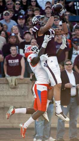 Texas A&M's Mike Evans (13) grabs a 13-yard touchdown pass over Sam Houston State's Dax Swanson (7) during the second quarter of an NCAA college football game, Saturday, Nov. 17, 2012, in College Station, Texas.  (Dave Einsel / Associated Press)