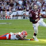 Texas A&M's Johnny Manziel (2) runs around Sam Houston State's Robert Shaw (23) for a touchdown during the second quarter of an NCAA college football game, Saturday, Nov. 17, 2012, in College Station, Texas.  (Dave Einsel / Associated Press)