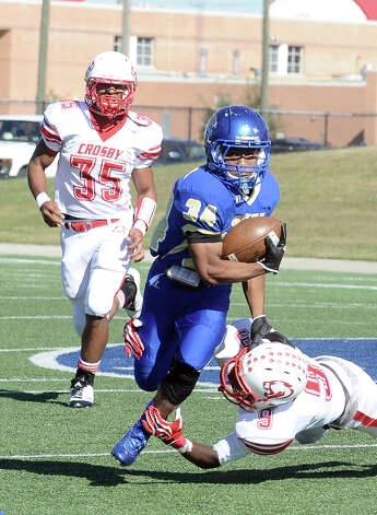 Ozen running back Xavier Johnes, 34, is taken down by Crosbys Darrian Manuel,9, during the Ozen High School Class 4A Division 1 first round game against Crosby High School at Galena Park ISD Athletic Complex on Saturday, November 17, 2012.  Photo taken: Randy Edwards/The Enterprise Photo: Randy Edwards