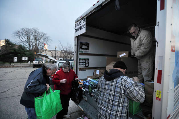 Brian Bardo, left, drops off a donation to Mary-Jane Mardis as Peter Viola, foreground, and Allen Mardis Jr., right, organize other donations at the Tunnel To Towers donation site in Danbury on Thursday, Nov. 15, 2012. Photo: Jason Rearick / The News-Times