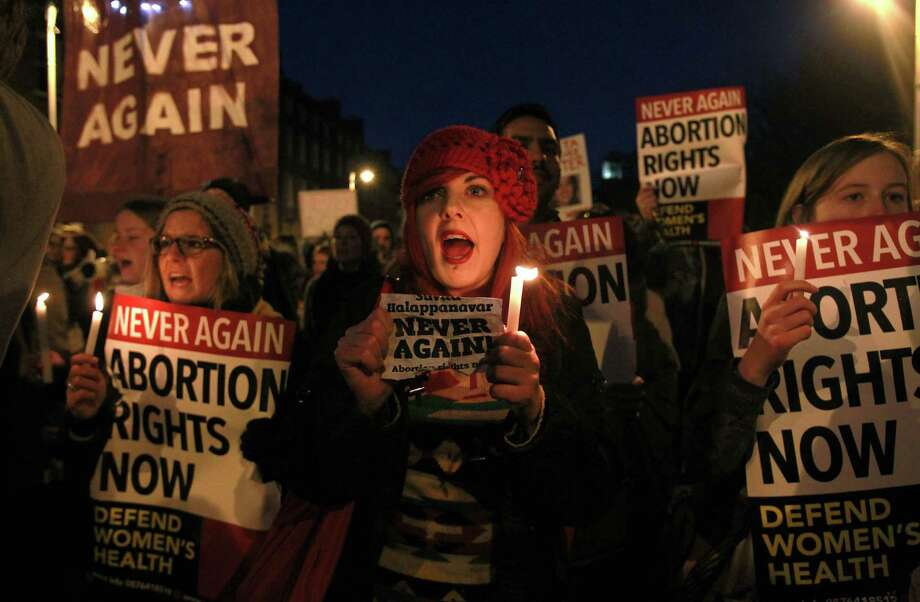 Demonstrators hold placards and candels in memory of Indian Savita Halappanavar in support of legislative change on abortion during a march from the Garden of Remembrance to the Dail (Irish Parliament) in Dublin, Ireland on November 17, 2012.  Ireland's tough abortion laws came under fire following the death of the Indian woman Halappanavar after doctors allegedly refused her a termination because it was against the laws of the Catholic country.  The Indian woman, who was 17 weeks pregnant, repeatedly asked the hospital to terminate her pregnancy because she had severe back pain and was miscarrying, her family said.     TOPSHOTS/AFP PHOTO/PETER MUHLYPETER MUHLY/AFP/Getty Images Photo: PETER MUHLY, AFP/Getty Images / AFP ImageForum