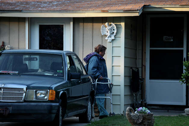 A woman who lives with Nancy Murrah, walks to Murrah's home, next to Murrah's former boarding house, Amistad Residential Facility, left, where four men were killed in a fire in August, on Friday, Nov. 16, 2012. Photo: Lisa Krantz, San Antonio Express-News / © 2012 San Antonio Express-News