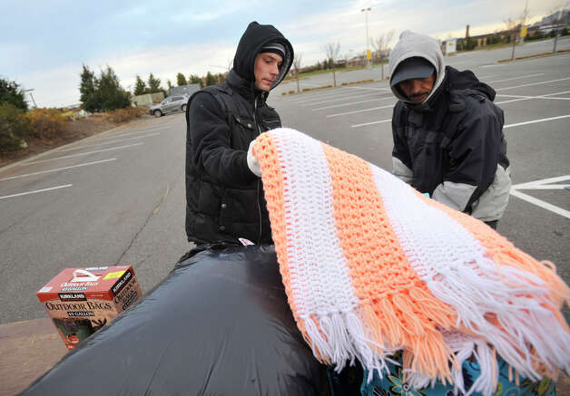 Brandon Chiarello, left, takes a hand-knitted afghan while looking for items his family needs with Candido Cabrera in the Ikea parking lot in the Red Hook section of Brooklyn, N.Y., on Friday, Nov. 16, 2012. The afghan was originally donated in New Milford. Photo: Jason Rearick / The News-Times