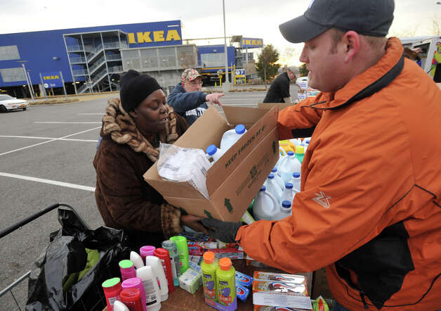 Red Hook resident Eva Hayes, left, receives cleaning supplies from Pastor Chris Lewis in the Ikea parking lot in the Red Hook section of Brooklyn, N.Y., on Friday, Nov. 16, 2012. Lewis is the pastor of Faith Church New York City. Photo: Jason Rearick / The News-Times