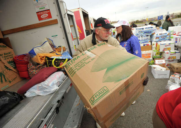 Allen Mardis hauls a box of donated goods from a U-Haul truck to the tables where residents affected by Hurricane Sandy could receive the donations in the Ikea parking lot in the Red Hook section of Brooklyn, N.Y., on Friday, Nov. 16, 2012. Photo: Jason Rearick / The News-Times