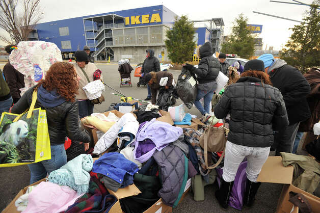 People look over donated clothes in the Ikea parking lot in the Red Hook section of Brooklyn, N.Y., on Friday, Nov. 16, 2012. The donated clothes were collected by volunteers from the Tunnel To Towers Foundation to aid New York City residents that were affected by Hurricane Sandy. Photo: Jason Rearick / The News-Times