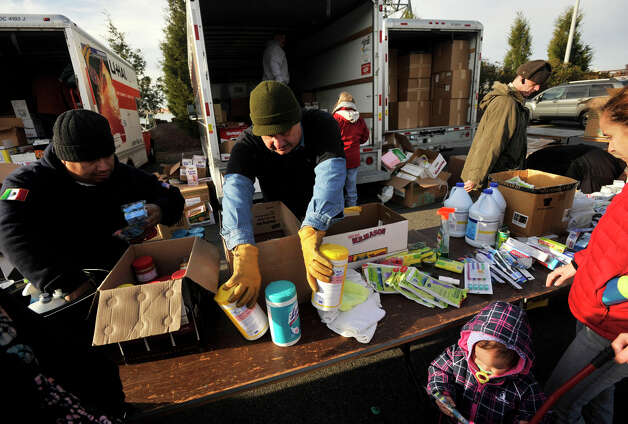 Jim Vigar replenishes sanitary wipes as people affected by Hurricane Sandy wait in line to receive donations in the Ikea parking lot in the Red Hook section of Brooklyn, N.Y., on Friday, Nov. 16, 2012. Photo: Jason Rearick / The News-Times