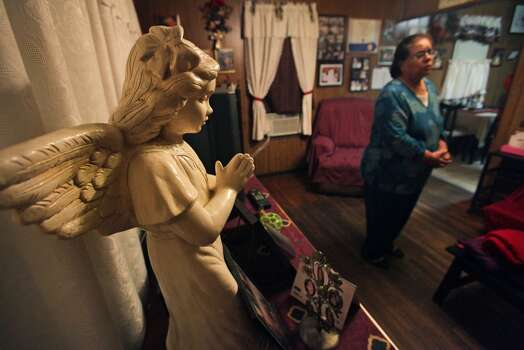 A statue of a praying angel stands near Maria Vasquez, right, in her living room where Vasquez prayed daily for her daughter Anna Vasquez.