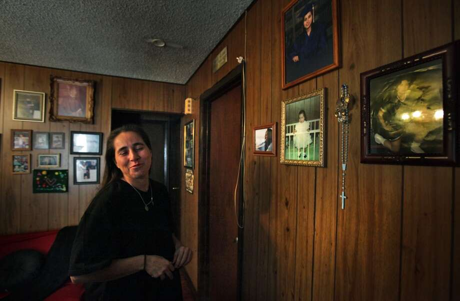 "Anna Vasquez, just released from prison, stops at the ""Anna Wall"" in her mother's home, joking that the photo of her in a crib as a baby, was the first picture of her behind bars."