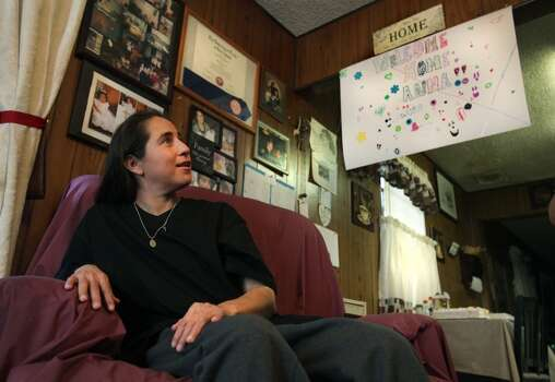 Anna Vasquez, just home after serving 12 and a half years in prison, admires family photos on the walls in her mother's home.